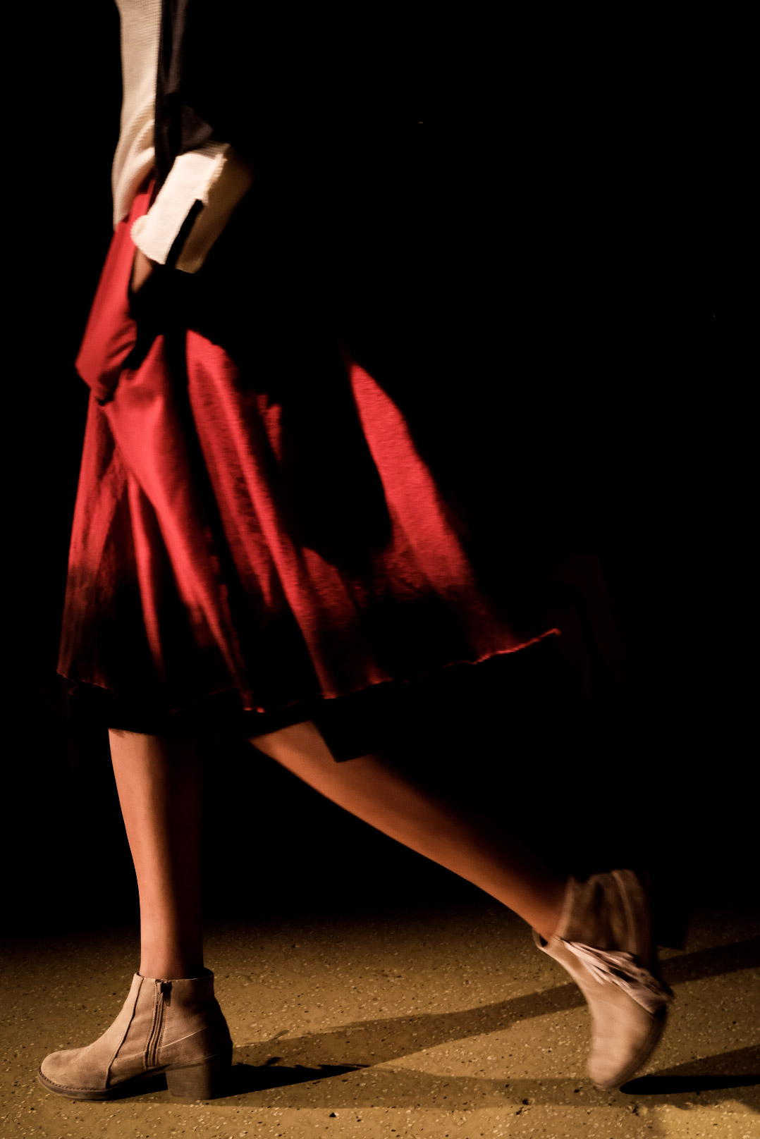 The bottom half of a model on the runway wearing a red flowy skirt during Local Coterie