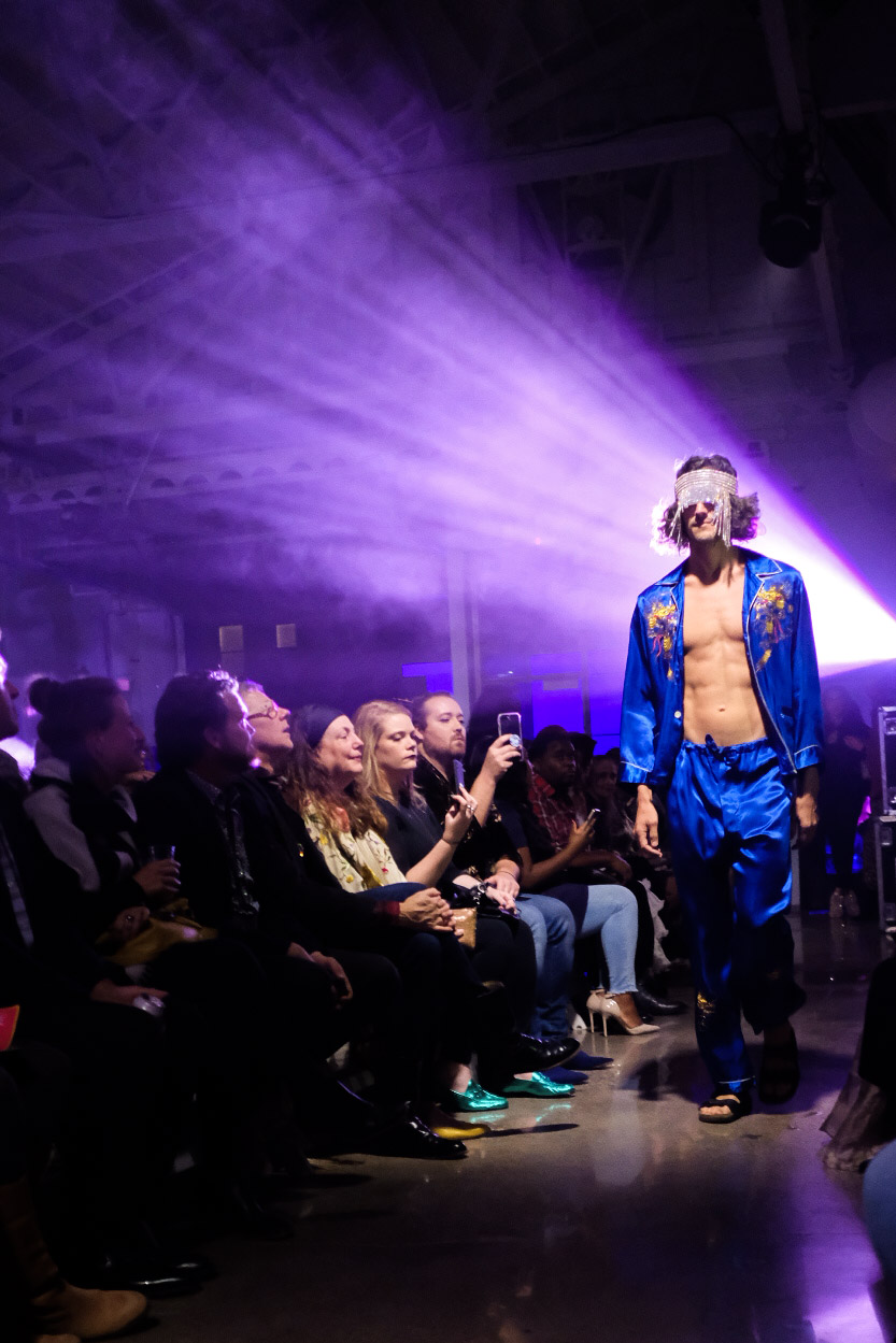 Male model walking down the runway in a blue silk ensemble